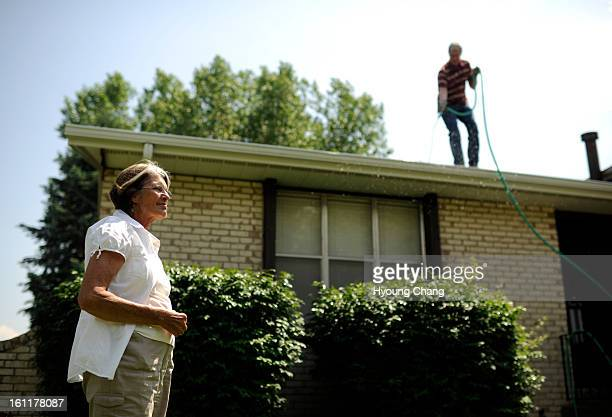 Wayne Bonnell right is cleaning out roof gutter of Helen Hutchinson left at Littleton Colo on Thursday June 7 2012 A new nonprofit called Village to...