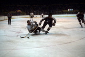 Wayne Cashman of the Boston Bruins is knocked down by Don Awrey of the New York Rangers circa 1977 at the Boston Garden in Boston Massachusetts