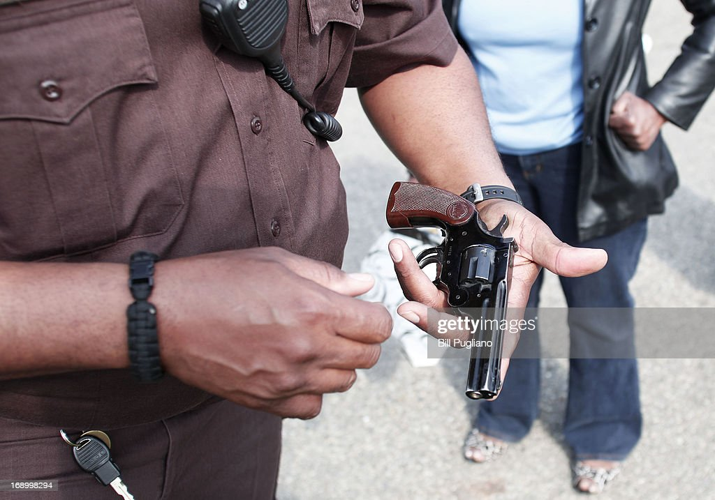 A Wayne County Sheriff's officer examines a gun a woman is bringing in to exchange for a $50 Meijer gift card at a 'Groceries For Guns' gun buyback program May 18, 2013 at the New St. Paul Tabernacle Church of God in Christ in Detroit, Michigan. The event was sponsored by the law firm Goodman Acker P.C. in a public-private partnership with Wayne County.