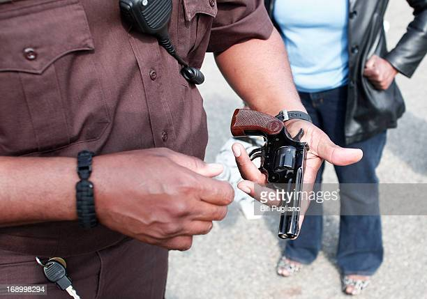 Wayne County Sheriff's officer examines a gun a woman is bringing in to exchange for a $50 Meijer gift card at a 'Groceries For Guns' gun buyback...