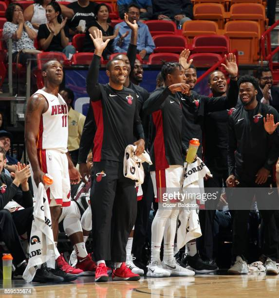 Wayne Ellington and Larry Drew II of the Miami Heat with their teammates react to a play against the Charlotte Hornets during the preseason game on...