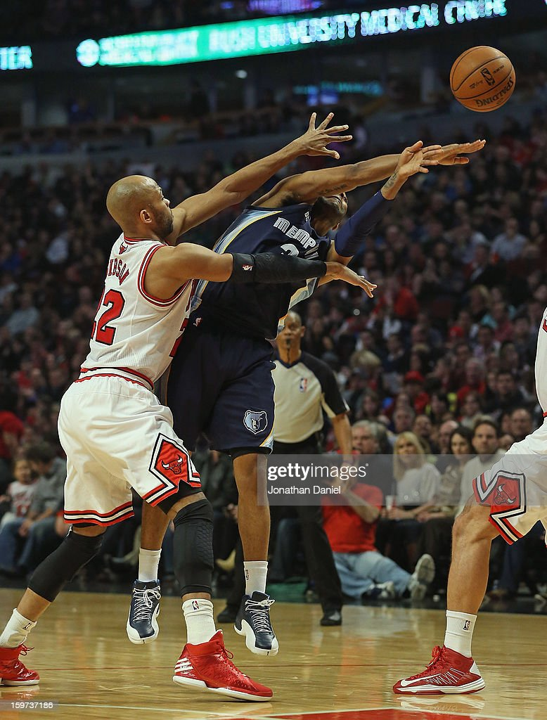 Wayne Ellington of the Memphis Grizzles passes under pressure from Taj Gibson of the Chicago Bulls at the United Center on January 19 2013 in Chicago...