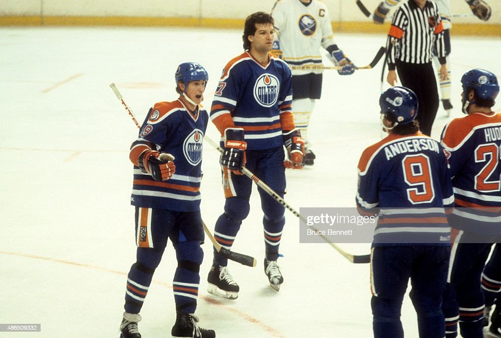 Wayne Gretzky #99 and Dave Semenko #27 of the Edmonton Oilers celebrate with teammates Glenn Anderson #9 and Charlie Huddy #22 during an NHL game against the Buffalo Sabres on February 24, 1982 at the Buffalo Memorial Auditorium in Buffalo, New York. (Photo by B Bennett/Bruce Bennett Studios/Getty Images