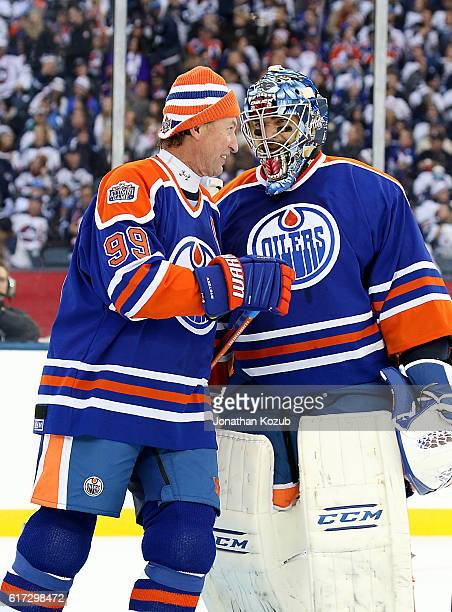Wayne Gretzky and goaltender Curtis Joseph of the Edmonton Oilers alumni chat during a third period stoppage in play in the 2016 Tim Hortons Heritage...
