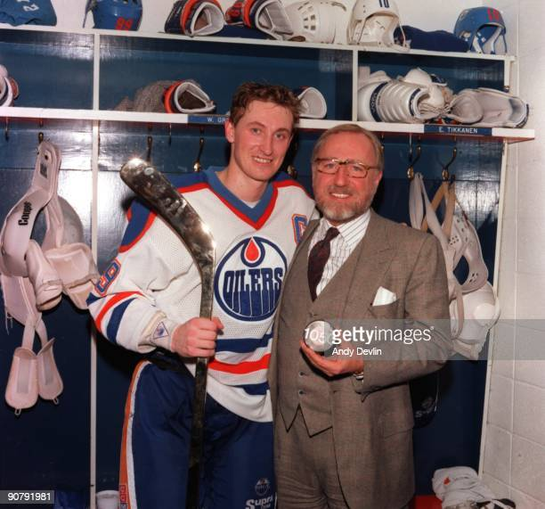 Wayne Gretzky and owner Peter Pocklington of the Edmonton Oilers pose for a photo in the locker room with Pocklington holding a puck with 1050 marked...