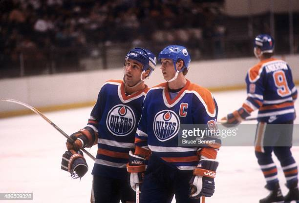 Wayne Gretzky and Paul Coffey of the Edmonton Oilers talk on the ice during an NHL game against the New York Rangers on March 28 1986 at the Madison...