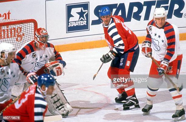 Wayne Gretzky of the Campbell Conference and the Los Angeles Kings stands on the side of the net as goalie Patrick Roy of the Wales Conference and...