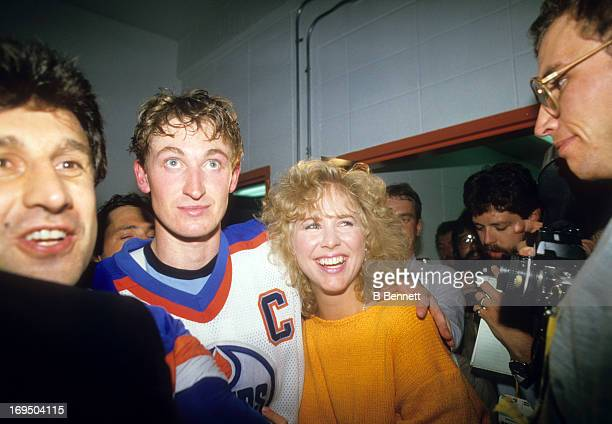 Wayne Gretzky of the Edmonton Oilers and his girlfriend Vicki Moss walk to the locker room after the Oilers defeated the Philadelphia Flyers in Game...
