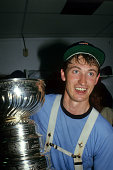 Wayne Gretzky of the Edmonton Oilers celebrates in the locker room with the Stanley Cup Trophy after the Oilers defeated the New York Islanders in...