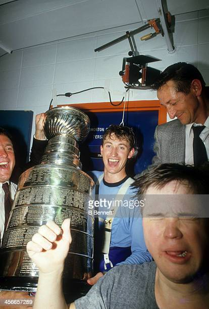 Wayne Gretzky of the Edmonton Oilers celebrates in the locker room with his father Walter Gretzky Joey Moss and the Stanley Cup Trophy after the...