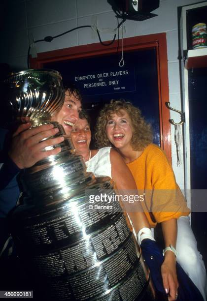 Wayne Gretzky of the Edmonton Oilers celebrates in the locker room with his girlfriend Vicki Moss and the Stanley Cup Trophy after the Oilers...
