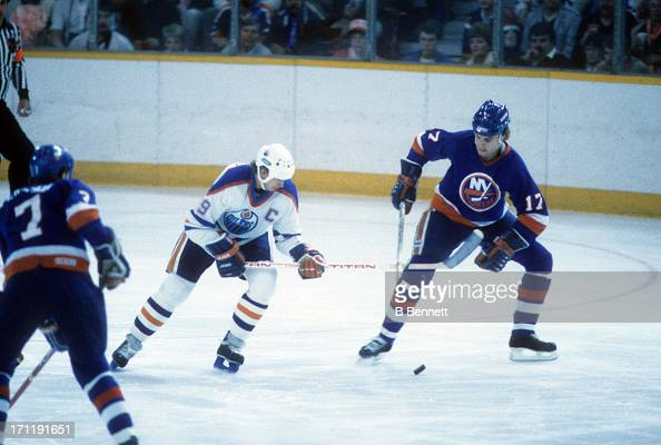 Wayne Gretzky of the Edmonton Oilers goes for the puck as Greg Gilbert of the New York Islanders defends during the 1984 Stanley Cup Finals in May...