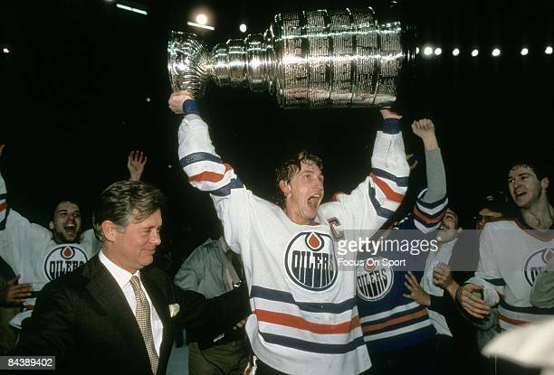 Wayne Gretzky of the Edmonton Oilers holds the Stanley Cup over his head after the Oilers defeated the New York Islanders in Game 5 of the 1984 NHL...