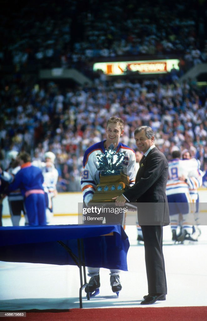 Wayne Gretzky of the Edmonton Oilers is presented the Conn Smythe Trophy from John Ziegler after the Edmonton Oilers defeated the Boston Bruins in...