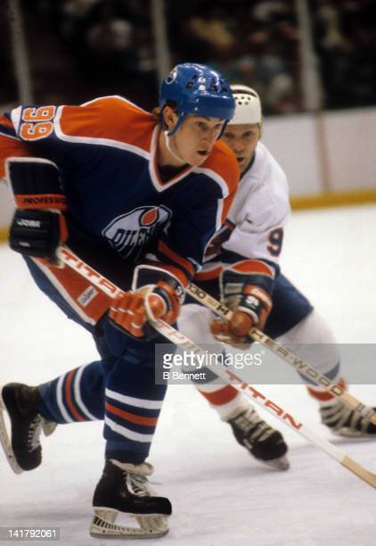 Wayne Gretzky of the Edmonton Oilers skates on the ice as Butch Goring of the New York Islanders defends during their game in 1984 at the Nassau...