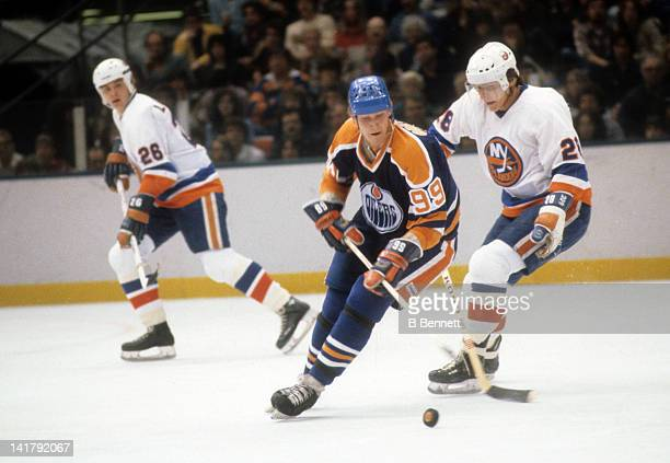 Wayne Gretzky of the Edmonton Oilers skates with the puck as Anders Kallur of the New York Islanders defends during their game in 1980 at the Nassau...