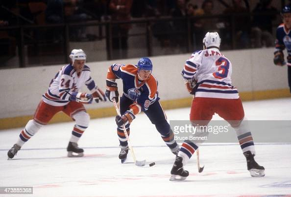 Wayne Gretzky of the Edmonton Oilers skates with the puck as he is defended by James Patrick of the New York Rangers on March 28 1986 at the Madison...