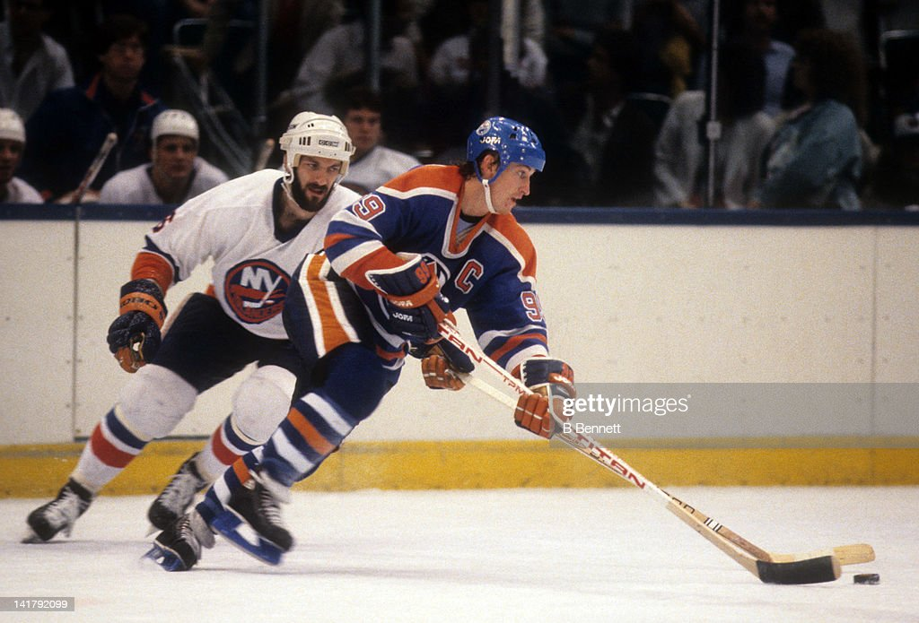 Wayne Gretzky of the Edmonton Oilers skates with the puck as Ken Morrow of the New York Islanders defends during the 1983 Stanley Cup Finals in May...