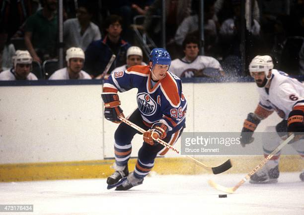 Wayne Gretzky of the Edmonton Oilers skates with the puck as Ken Morrow of the New York Islanders goes for the poke check circa 1984 at the Nassau...