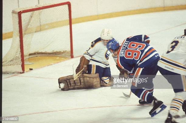 Wayne Gretzky of the Edmonton Oilers slips the puck past goalie Don Edwards of the Buffalo Sabres for his 77th goal of the season during their game...
