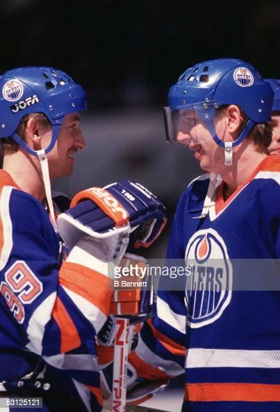 Wayne Gretzky of the Edmonton Oilers talks with teammate Jari Kurri during an NHL game circa 1987