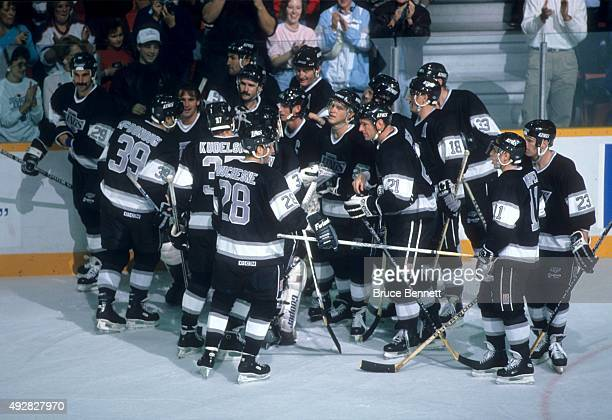 Wayne Gretzky of the Los Angeles Kings is mobbed by teammates along the boards after he scored his 1851st career NHL point against the Edmonton...
