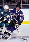 Wayne Gretzky of the Western Conference and the Los Angeles Kings skates on the ice as he is defended by Adam Oates of the Eastern Conference and the...