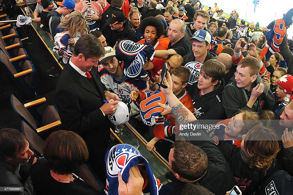 Wayne Gretzky sings autographs for fans during a game between the Edmonton Oilers and the New York Islanders on March 6, 2014 at Rexall Place in Edmonton, Alberta, Canada.