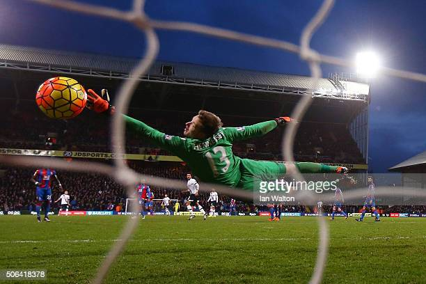 Wayne Hennessey of Crystal Palace dives in vain as Nacer Chadli of Tottenham Hotspur scores his team's third goal during the Barclays Premier League...