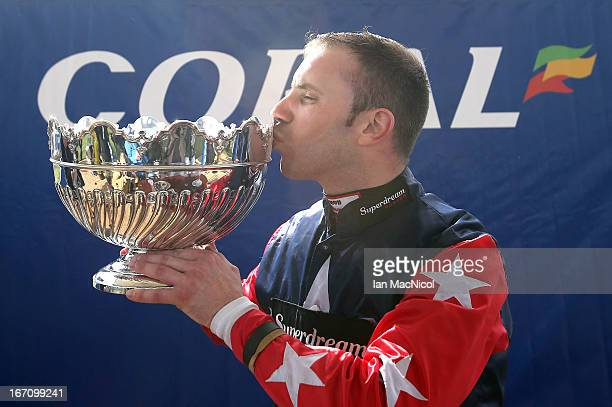 Wayne Hutchinson kisses his trophy after he wins The Coral Scottish Grand National Handicap Steeple Chase on Godsmejudge at Ayr racecourse on April...