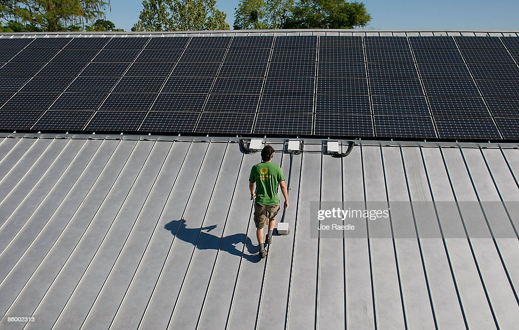 Wayne Irwin, who works for Pure Energy Solar, works on the installation of a solar panel system on the roof of a business on April 15, 2009 in Gainesville, Florida. Recently the city of Gainesville through a program initiated by the local Gainesville Regional Utilities became the first city in the nation to have a solar feed-in tariff ordinance which means owners of new solar photovoltaic systems will be eligible to receive 32 cents per kilowatt hour of electricity produced by the system over the next 20 years. The new program has produced a spurt of solar installation projects around the city. Other states and cities around the nation are eyeing the feed-in tariff program as a renewable energy program they might be interested in doing.