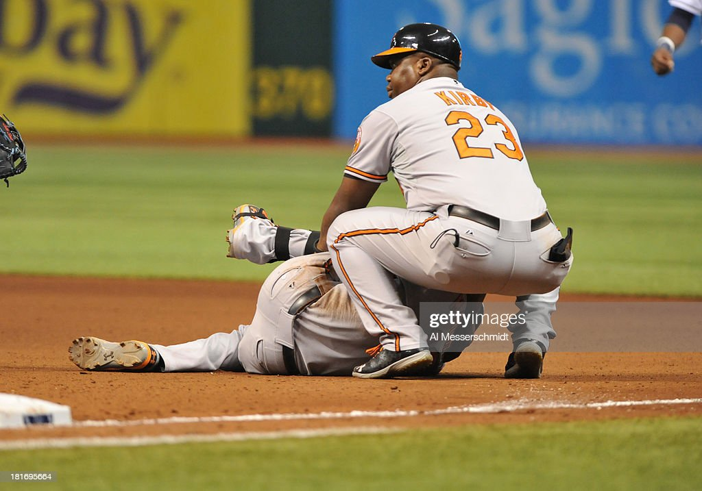 Wayne Kirby #23 checks on Infielder Manny Machado #13 of the Baltimore Orioles after he twisted a knee on first base in the 7th inning against the Tampa Bay Rays September 23, 2013 at Tropicana Field in St. Petersburg, Florida. Coach Wayne Kirby holds Machado.
