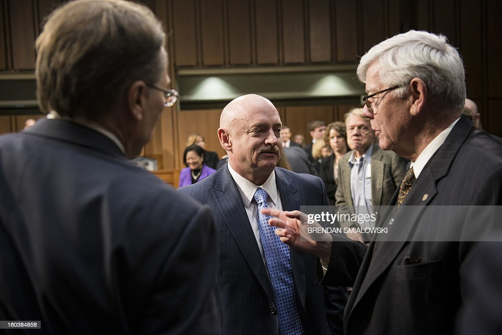 Wayne LaPierre (L), Chief Executive Officer of the National Rifle Association(NRA), and David A. Keene (R), President of the National Rifle Association, speak with retired Astronaut Mark Kelly, husband of former Arizona Rep. Gabrielle Giffords after a hearing of the Senate Judiciary Committee on Capitol Hill January 30, 2013 in Washington, DC. The committee held the hearingsabout solutions to gun violence in the United States. AFP PHOTO/Brendan SMIALOWSKI