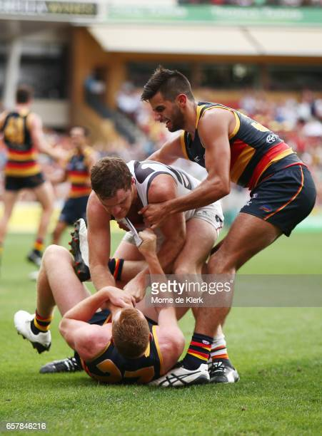 Wayne Milera of the Crows helps teammate Tom Lynch after a scuffle with Heath Shaw of the Giants during the round one AFL match between the Adelaide...