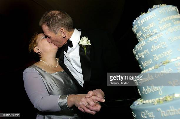 Wayne Nicolle and his new wife Kim steal a kiss as they cut their wedding cake on Saturday The cake had the names of all those attending their...