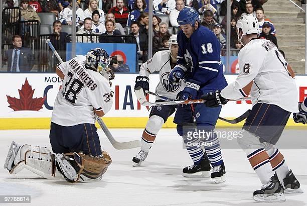 Wayne Primeau of the Toronto Maple Leafs grabs a rebound in the stomach against Jeff Deslauriers of the Edmonton Oilers during game action March 13...