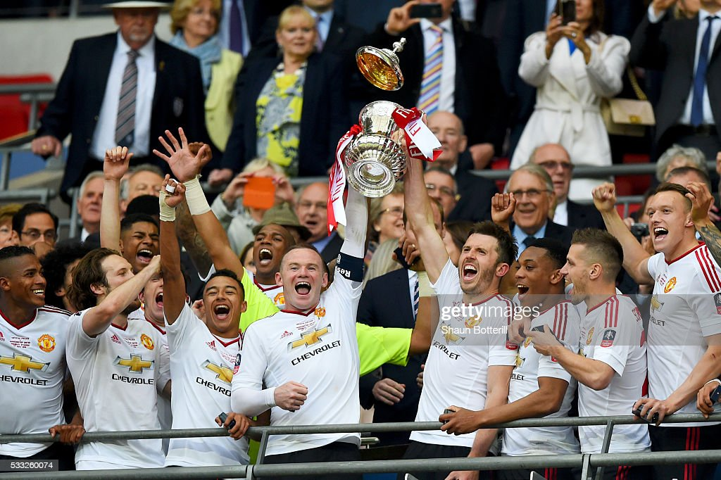 Wayne Rooney and Michael Carrick of Manchester United lift the trophy after winning The Emirates FA Cup Final match between Manchester United and...