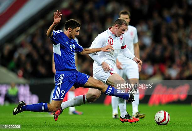 Wayne Rooney captain of England battles for the ball with Michele Cervellini of San Marino during the FIFA 2014 World Cup Group H qualifying match...