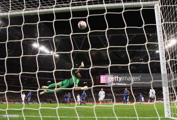 Wayne Rooney captain of England shoots at goal as Aldo Junior Simoncini of San Marino dives to his right during the FIFA 2014 World Cup Group H...