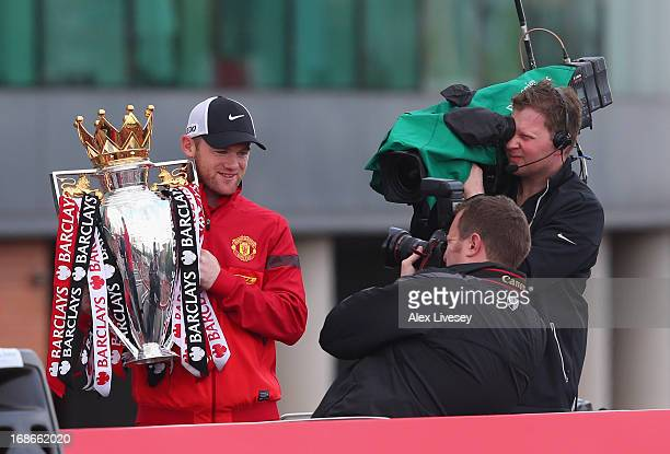 Wayne Rooney holds the Barclays Premier League Trophy aloft on the open topped bus outside Old Trafford during the Manchester United Premier League...
