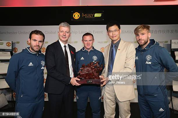 Wayne Rooney Juan Mata and Luke Shaw and Director of Communications Phil Townsend of Manchester United pose with CEO James Ni of Mlily at the launch...