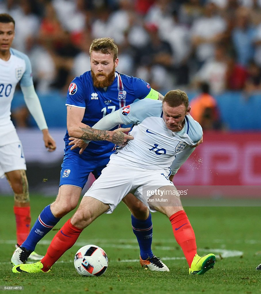 <a gi-track='captionPersonalityLinkClicked' href=/galleries/search?phrase=Wayne+Rooney&family=editorial&specificpeople=157598 ng-click='$event.stopPropagation()'>Wayne Rooney</a> of England and <a gi-track='captionPersonalityLinkClicked' href=/galleries/search?phrase=Aron+Gunnarsson&family=editorial&specificpeople=5490377 ng-click='$event.stopPropagation()'>Aron Gunnarsson</a> of Iceland compete for the ball during the UEFA EURO 2016 round of 16 match between England and Iceland at Allianz Riviera Stadium on June 27, 2016 in Nice, France.