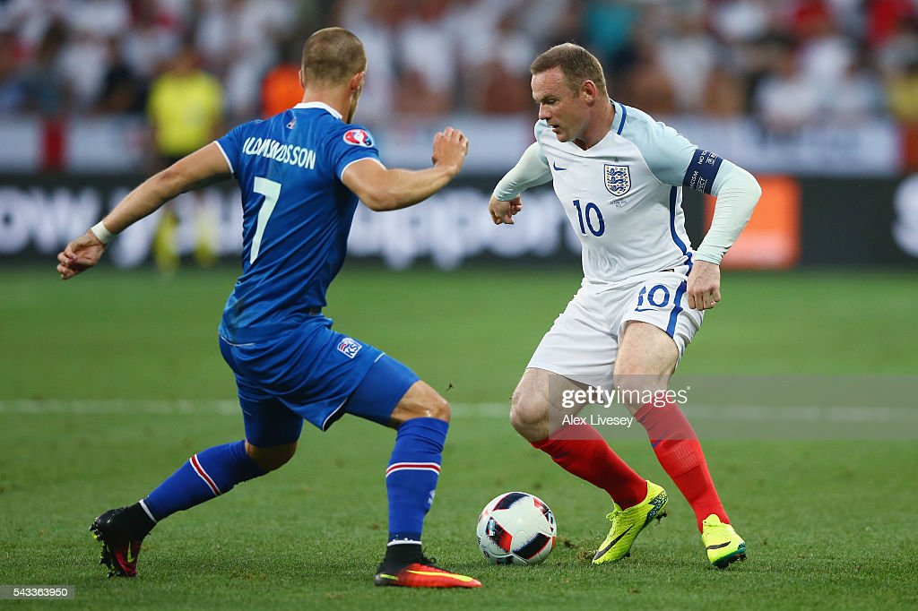 <a gi-track='captionPersonalityLinkClicked' href=/galleries/search?phrase=Wayne+Rooney&family=editorial&specificpeople=157598 ng-click='$event.stopPropagation()'>Wayne Rooney</a> of England and Johann Gudmundsson of Iceland compete for the ball during the UEFA EURO 2016 round of 16 match between England and Iceland at Allianz Riviera Stadium on June 27, 2016 in Nice, France.