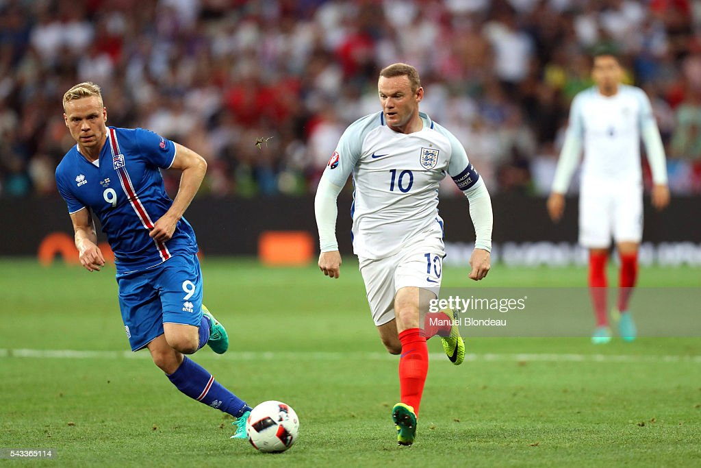 Wayne Rooney of England and Kolbeinn Sigthorsson of Iceland during the European Championship match Round of 16 between England and Iceland at Allianz Riviera Stadium on June 27, 2016 in Nice, France.