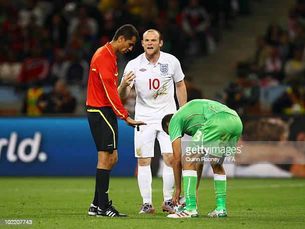 Wayne Rooney of England argues with referee Ravshan Irmatov as Nadir Belhadj of Algeria picks up the ball during the 2010 FIFA World Cup South Africa...