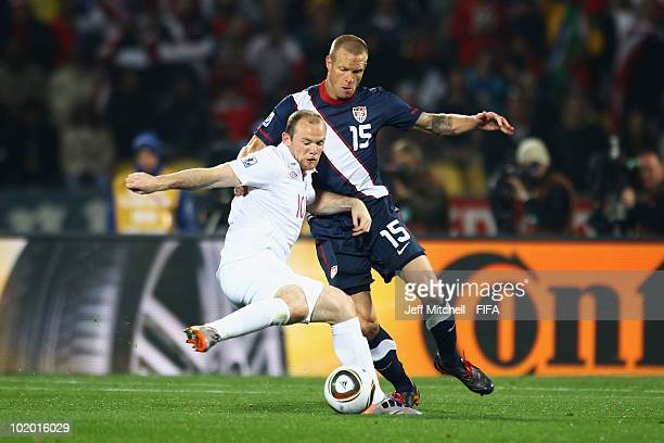 Wayne Rooney of England battles for the ball with Jay Demerit of the United States during the 2010 FIFA World Cup South Africa Group C match between...