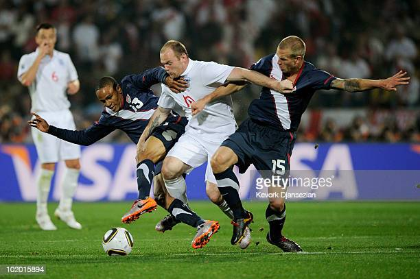Wayne Rooney of England battles for the ball with Ricardo Clark and Jay Demerit of the United States during the 2010 FIFA World Cup South Africa...