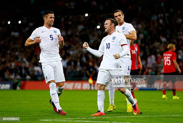 Wayne Rooney of England celebrates with Gary Cahill and Jordan Henderson of England after scoring the opening goal from the penalty spot during the...