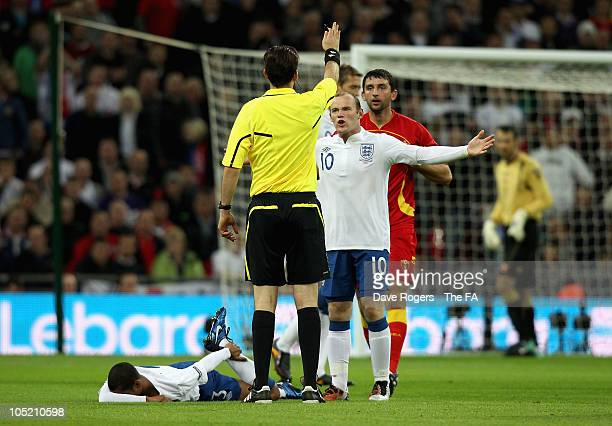 Wayne Rooney of England exchanges words with Referee Manuel Grafe after Ashley Cole was fouled during the UEFA EURO 2012 Group G Qualifying match...