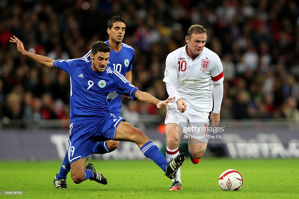 <a gi-track='captionPersonalityLinkClicked' href=/galleries/search?phrase=Wayne+Rooney&family=editorial&specificpeople=157598 ng-click='$event.stopPropagation()'>Wayne Rooney</a> of England goes past the challenge from Michele Cervellini of San Marino during the FIFA 2014 World Cup Group H qualifying match between England and San Marino at Wembley Stadium on October 12, 2012 in London, England.